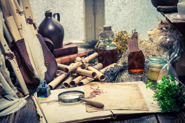 Rustic witch workshop with old scrolls and plants stock photo