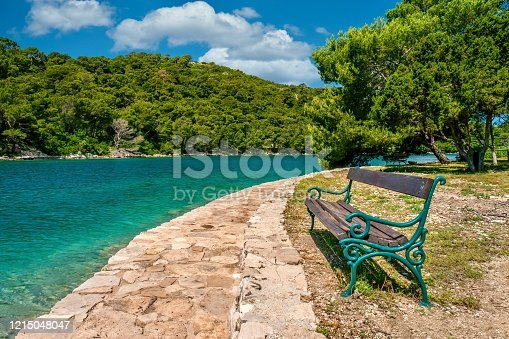 A beautiful, tranquil scene with a vintage park bench made of weathered wood and painted cast iron facing a stone pathway and  clear, turquoise water. Green, forested land and a vibrant blue sky with fluffy clouds are in the background.