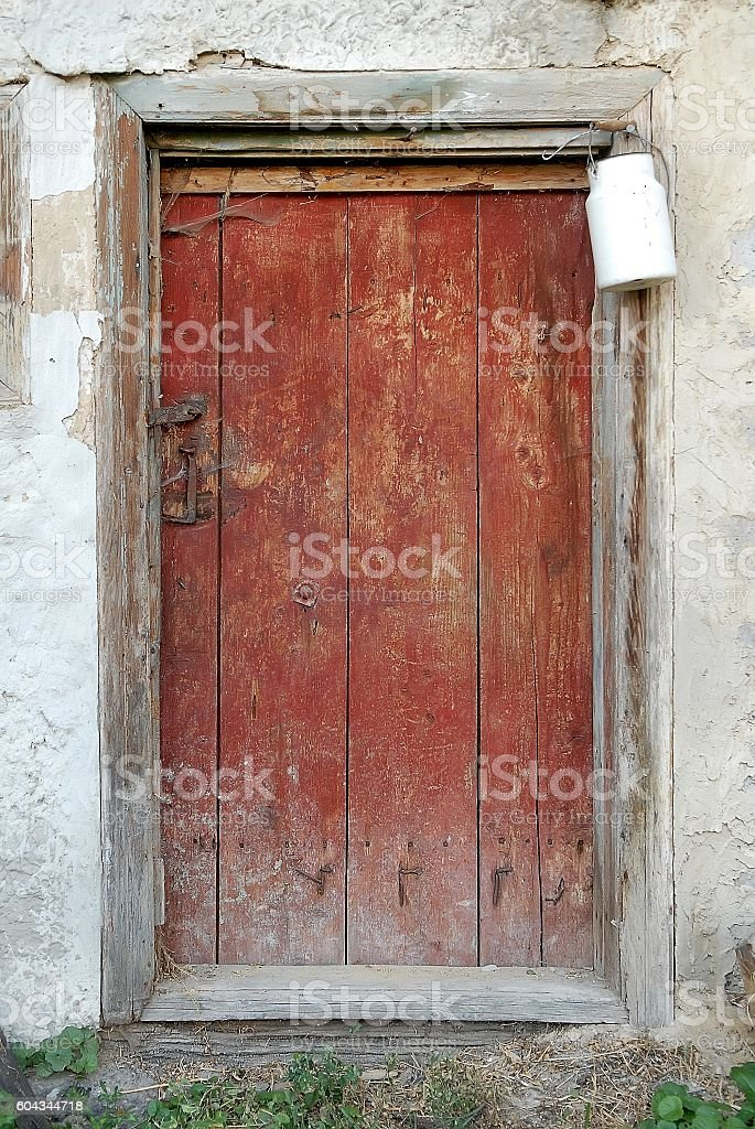Rustic wooden barn door with white milk can stock photo