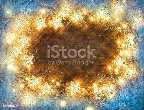 636659848 istock photo Rustic wooden board with snowflakes and garland 636659792