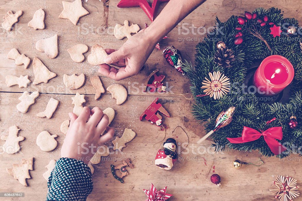 rustic wooden christmas table with hands holding selfmade cookies ストックフォト