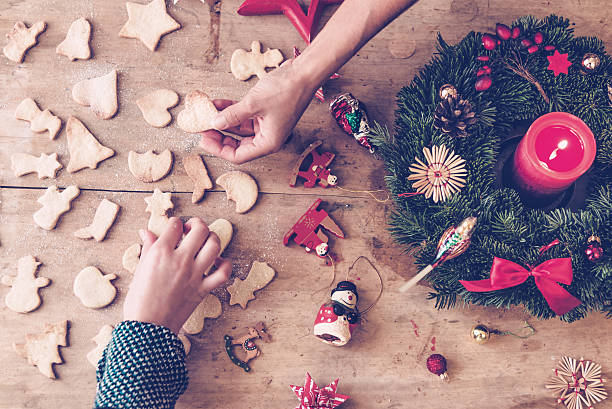 rustic wooden christmas table with hands holding selfmade cookies - 降臨節 ストックフォトと画像