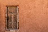 istock Rustic Wooden Door on Adobe Building Wall 929775580