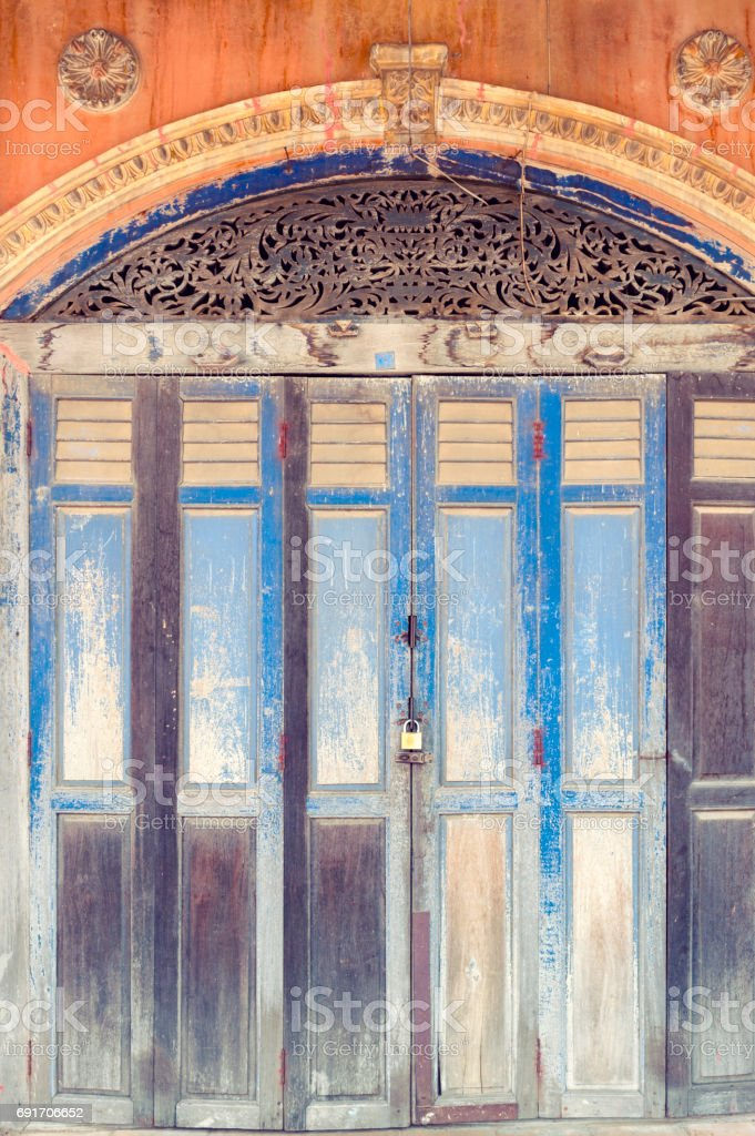 Rustic wooden folding doors in front of classic Sino-Portuguese architectural style shophouse building at Ban Singha Tha, old historic area of Yasothon Province in the northeastern region of Thailand stock photo