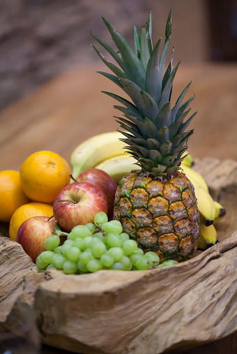 Rustic wooden fruit bowl with pineapple,bananas,apples and oranges