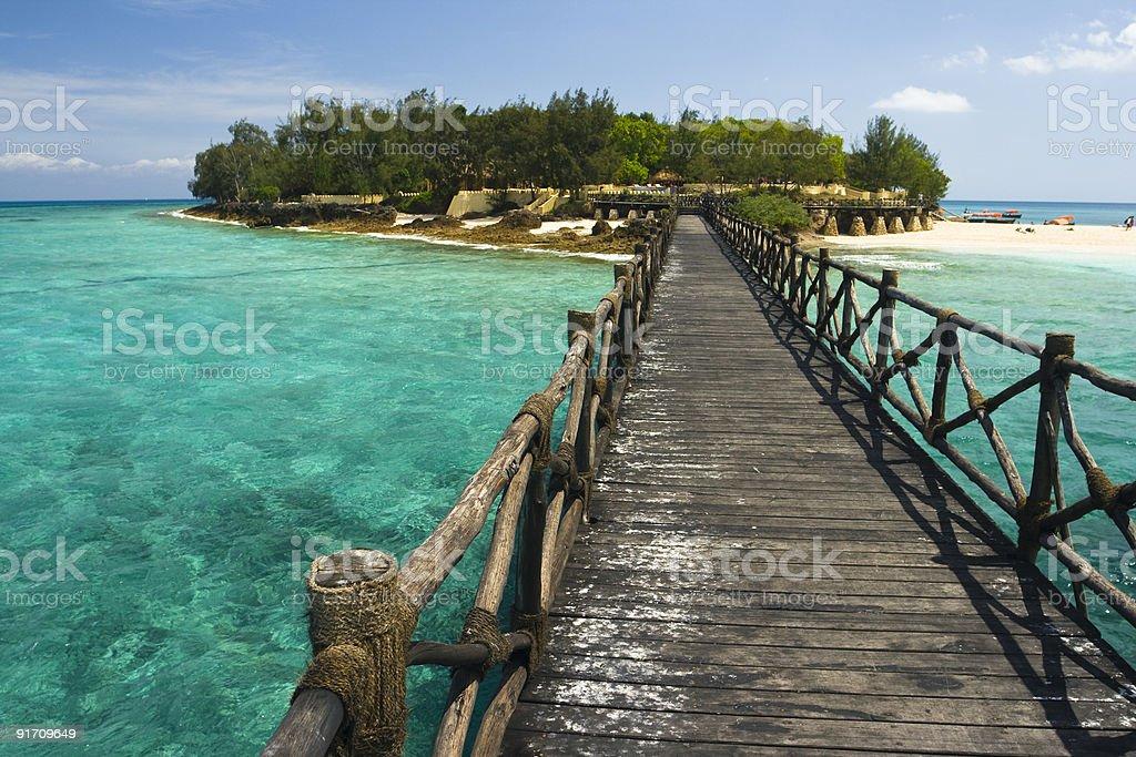 Rustic wooden prison island bridge on clear blue ocean water stock photo