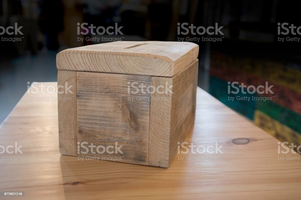 Rustic wooden shop made collection box made from chunky wood and resting on wooden table stock photo
