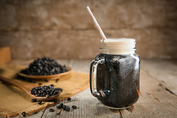 Rustic wooden table and background nitro coffee espresso jar straw Fresh from the tap nitrous infused dark rich nitro black coffee in a glass jar java creamy beautiful froth foam head lifestyle decor with roasted beans on a rustic reclaimed wood wooden table background nitrogen stock pictures, royalty-free photos & images
