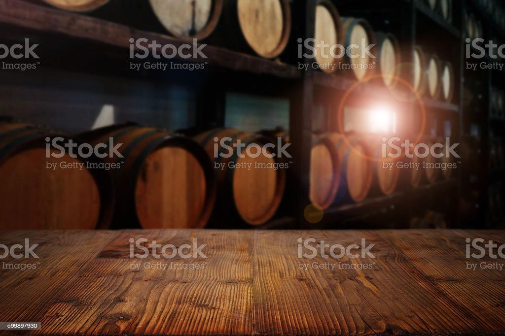 Rustic wooden table in a wine cellar stock photo