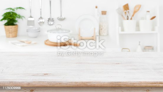 923629650istockphoto Rustic wooden table top on blurred kitchen shelf background 1129309966