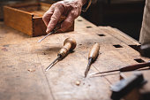 A wooden workbench with several tools for wood carving. A mature hand is holding another tool.