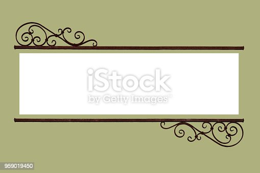 A decorative rustic old wrought iron frame information sign with a   blank white copy space for text announcement centered on a warm green background.  The metal decoration is rusty retro style nostalgic curls with straight bars across.