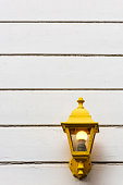 Rustic yellow lamp attached outside a house on white wall in Istanbul, Turkey.