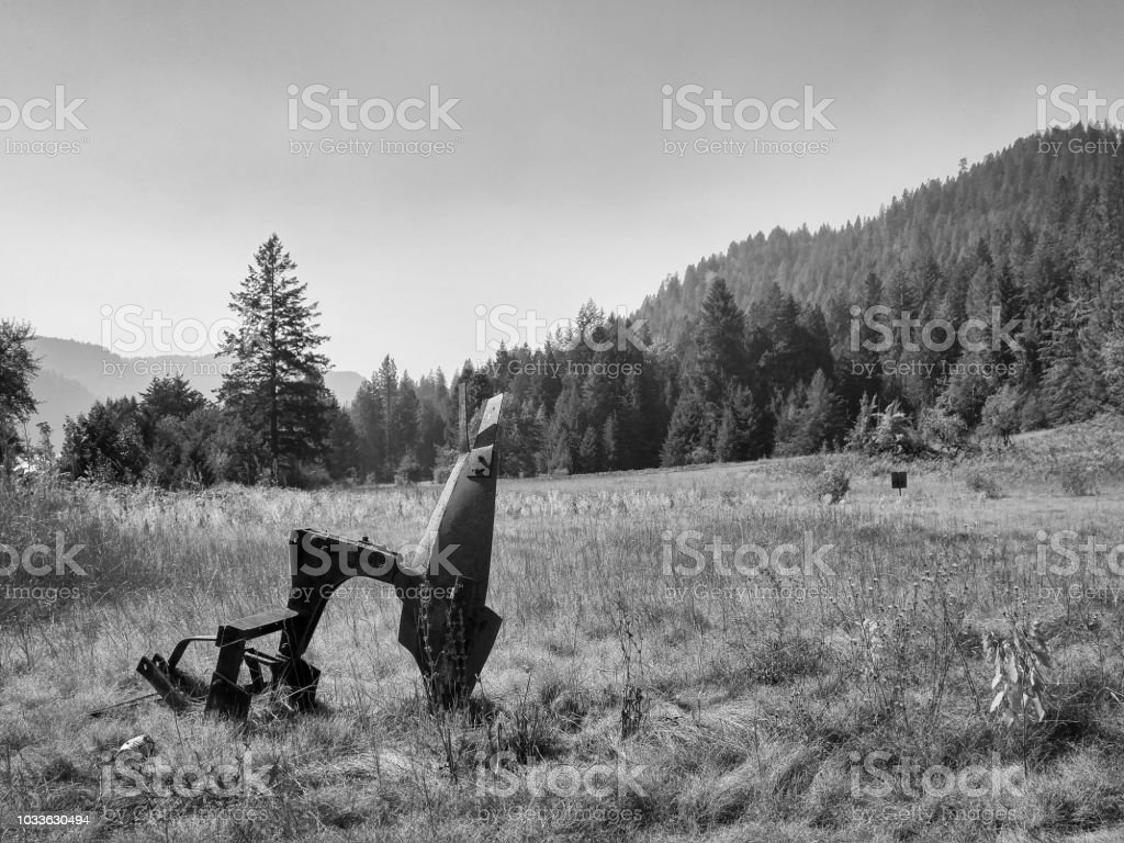 Rusting farm equipment in a dry field of grass by the mountains stock photo