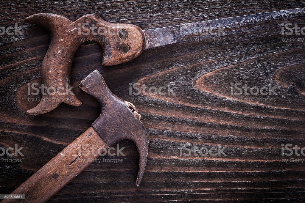 Rusty age-old handsaw with claw hammer on vintage dark stock photo