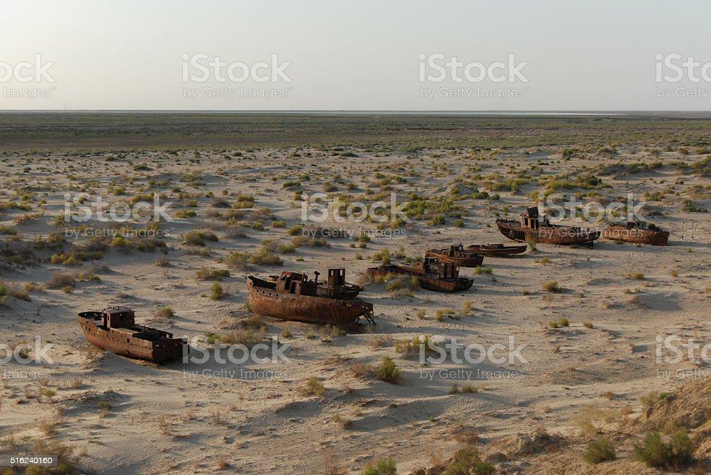 Rusty Aral fishing fleet lying in the sand stock photo