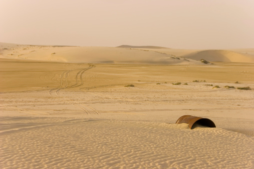 An oil barrel in Qatar in the middle of the desert. A place of emptyness