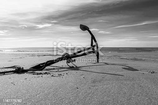 istock Rusty boat anchor on the beach 1167775762