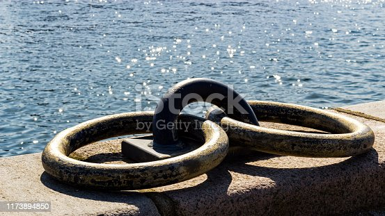 Low angle view of two rusty weathered mooring rings on stone wall beside water