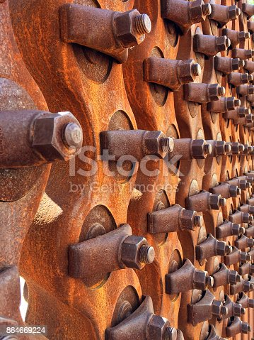 Rows and rows of rusted bolts attached to a metal plate.