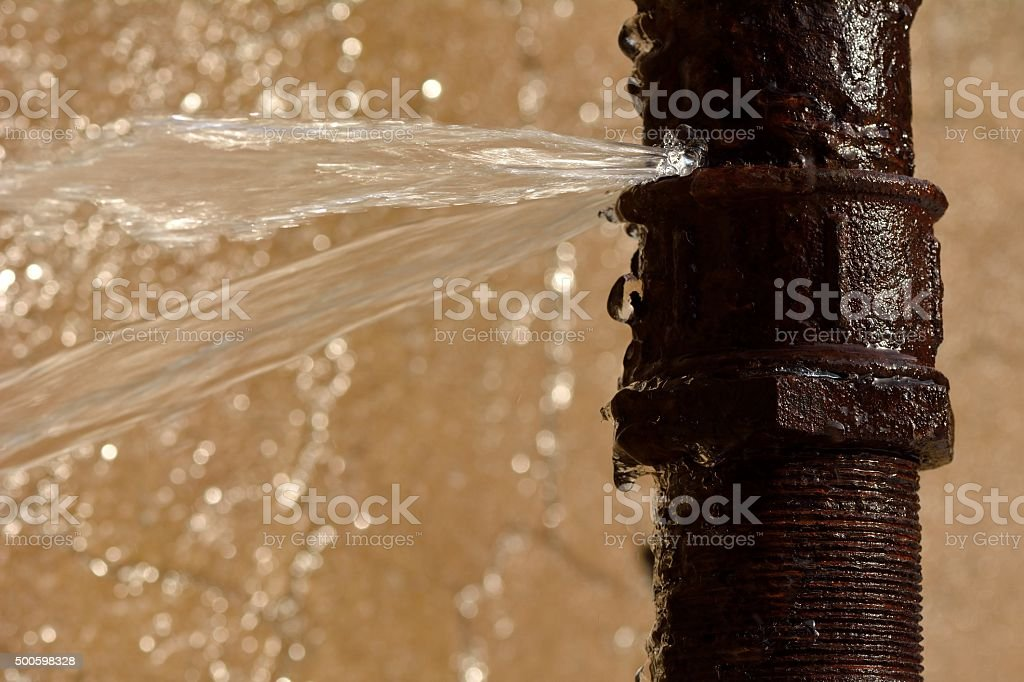 Rusty burst pipe in Baku Botanic Garden stock photo