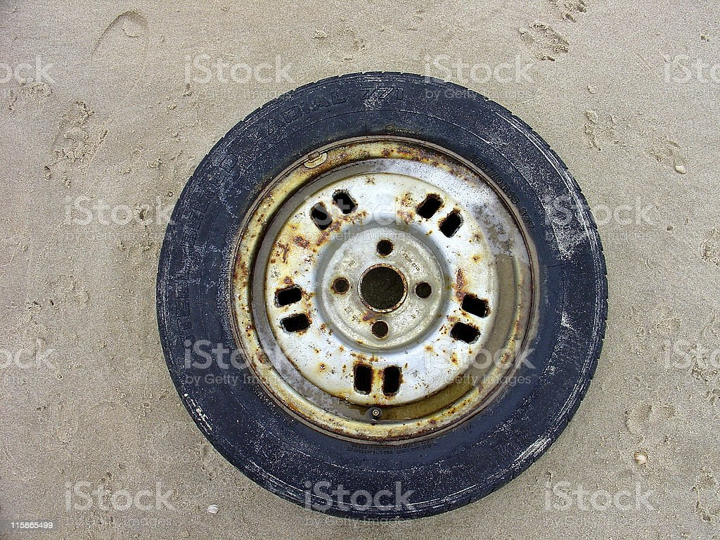 Rusty Car Tire on the Beach royalty-free stock photo
