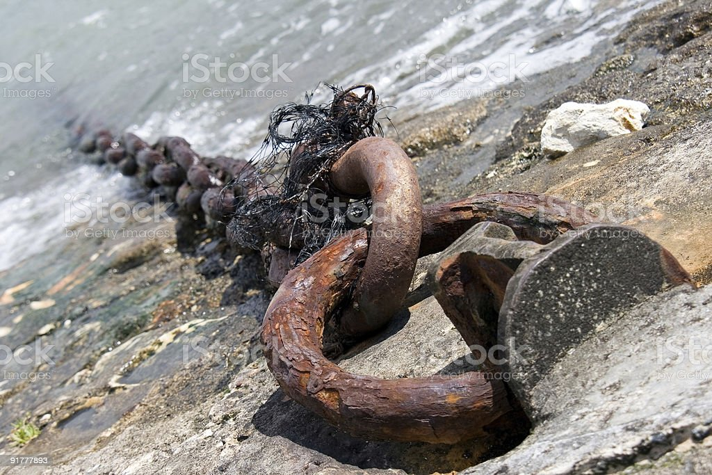 Rusty chain on a dock leading into the sea royalty-free stock photo