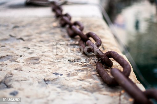 Close up photo of a rusty chain on the concrete ground.