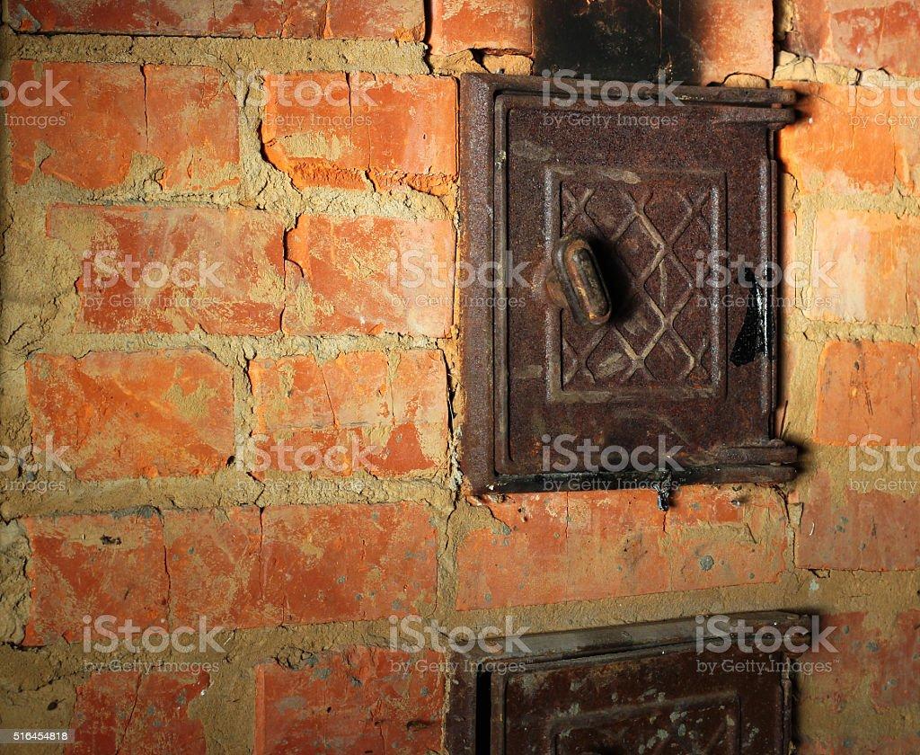 Rusty closed metal door in red brick sooty furnace stock photo