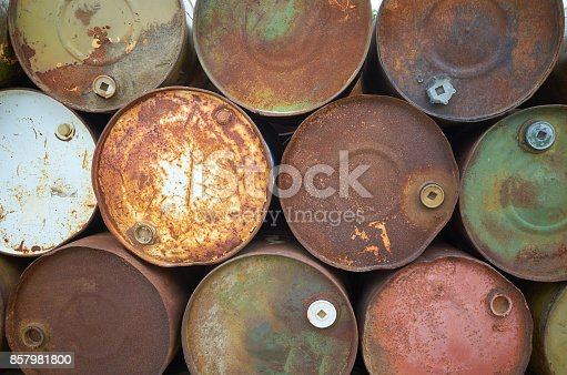istock Rusty colors metal barrels stacked in rows 857981800