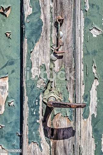 Close-up of a rusty steel door knob and hook on a weathered wooden door with peeling reen paint