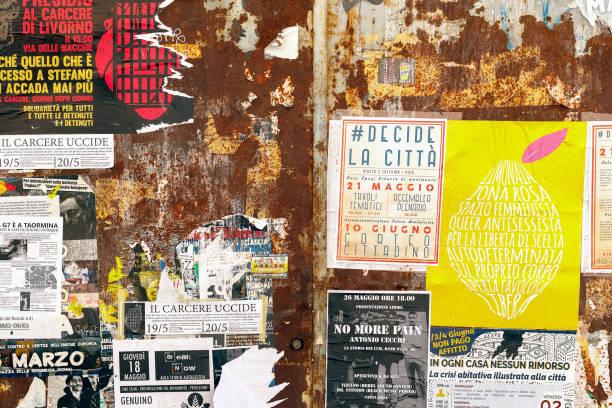rostiga dörrar omfattas av sönderrivna promotion affischer och klistermärken på en stadsgata av pisa - italy poster bildbanksfoton och bilder
