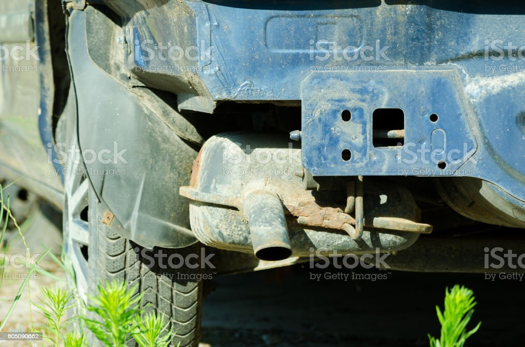 Rusty exhaust pipe on damaged car without rear bumper. stock photo