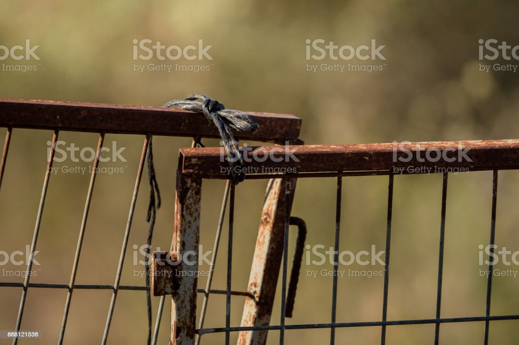 Rusty gate tied with a cord stock photo