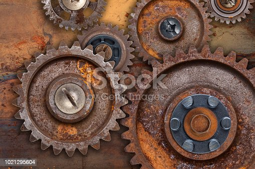 A collection of connected rusty gears over a rusty metal background.