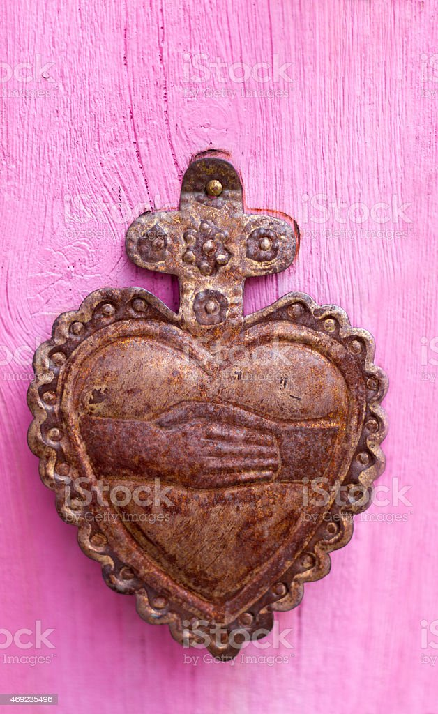Rusty Heart Milagro Votive on Pink Wood Background (Close-Up) stock photo