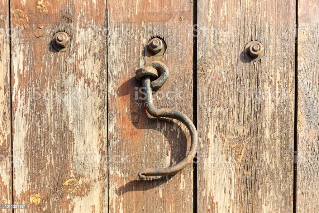 Gancho enferrujado pendurado em uma porta de madeira. Close-up vista. - foto de acervo