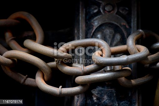 Rusty iron chain on closed vintage entrance gate