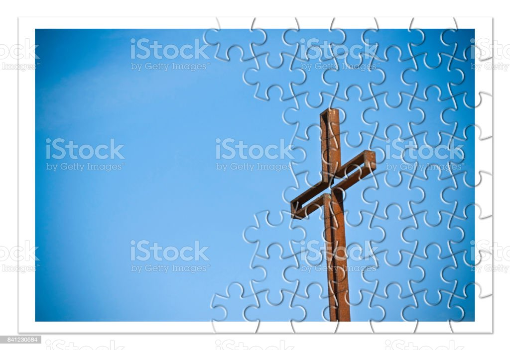 Rusty iron cross against a blue background - Rebuild our faith - Christian cross concept image in jigsaw puzzle shape. stock photo