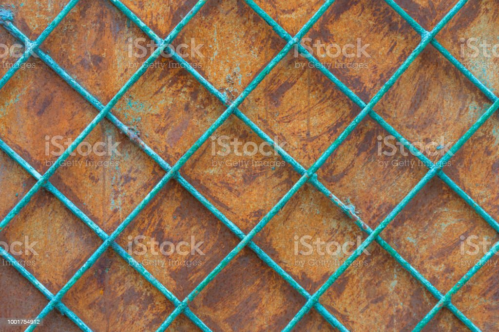 Rusty iron wall behind a metal painted lattice stock photo