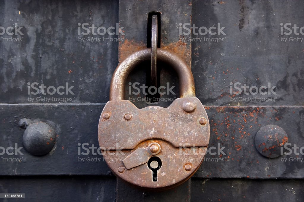 A rusty lock on a metal medieval door royalty-free stock photo