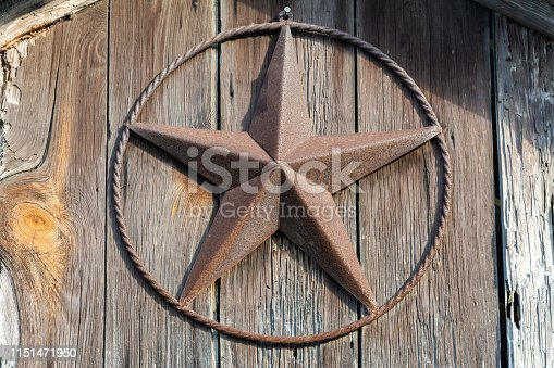 Rusty Lone Star sign on a wooden door in Texas.