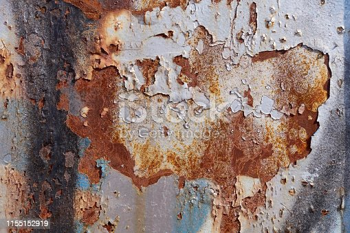 Photograph of a rusty steel door with peeling paint.
