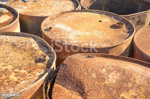 istock Rusty metal barrels stacked in rows 874282670