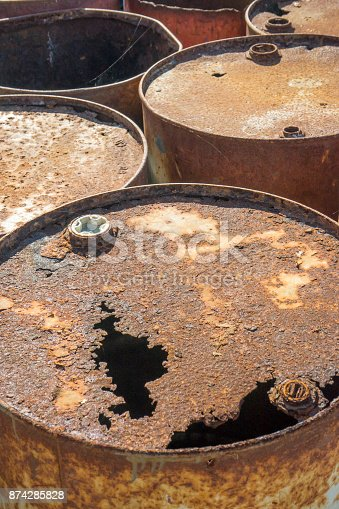 istock Rusty metal barrels stacked in rows 874285828