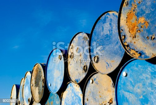 Batch of old rusty barrels against the blue sky