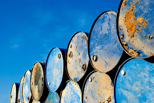 Rusty metal barrels stacked in rows Batch of old rusty barrels against the blue sky hazardous chemicals stock pictures, royalty-free photos & images