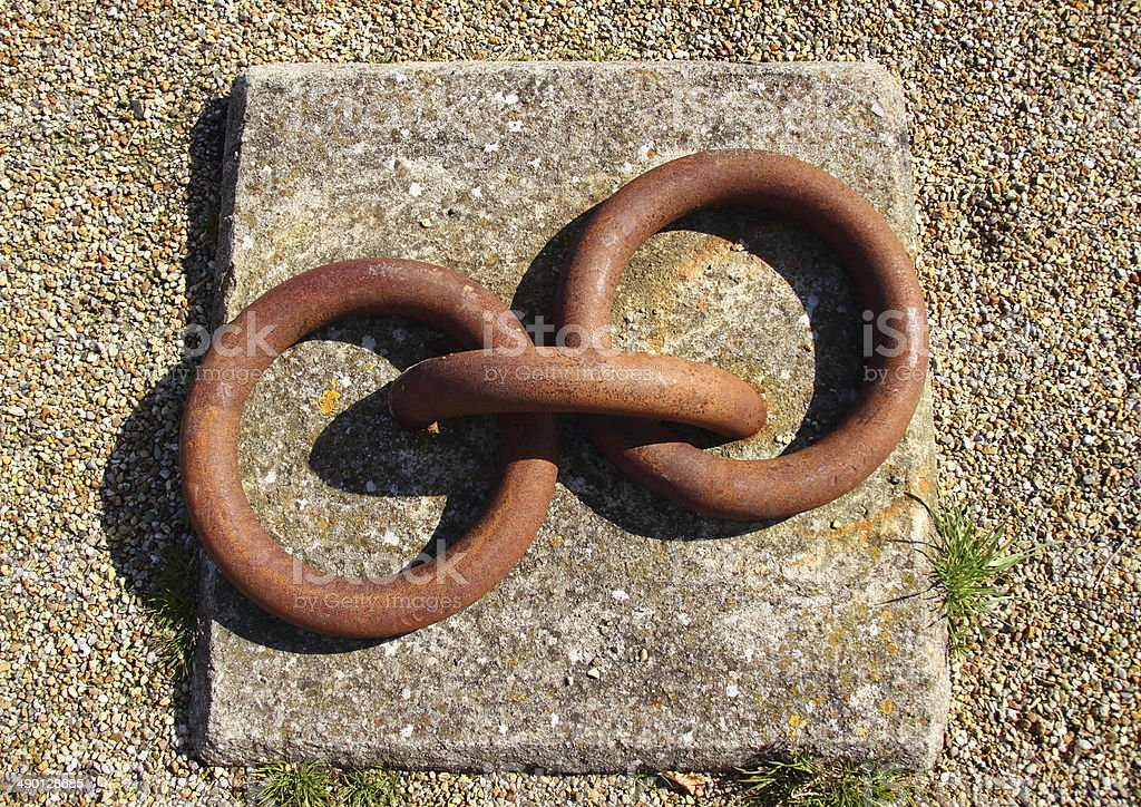 Rusty metal bollard rings mounted to concrete block isolated royalty-free stock photo