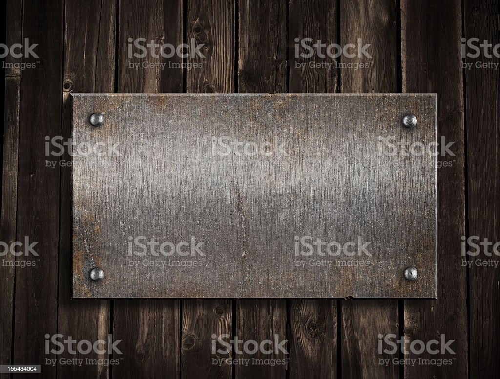 rusty metal plate on wooden background royalty-free stock photo
