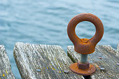 A rusty metal ring on a bolt mounted on a wooden pier.